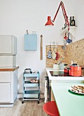 Fifties pastels paired with 70s orange in youthful, retro collectors' kitchen with old-fashioned kitchen dresser and DIY elements