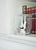 Raving Rabbid figurine under upturned preserving jar in front of books with high-quality bindings on shelf of old kitchen dresser