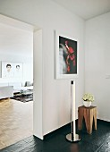 Tube Light Bauhaus standard lamp next to Backenzahn stool on slate-style floor covering; view of white couch through open doorway