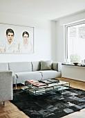 Coffeetable aus Glas auf Kuhfell Patchwork Teppich, elegante, moderne Couch in Hellgrau, vor Wandbild mit Männer- & Frauenmotv