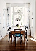 Rustic dining set with dark wood chairs and retro arc lamp in window niche
