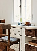 Old wooden chair with seat cushion in front of custom, vintage base units with drawers below window