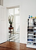 Half-height, glass-fronted cabinet painted white next to open door with view into foyer with chequered floor
