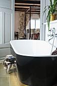 Free-standing bathtub with black outside in rustic bathroom