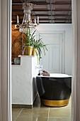 Blick durch offene Tür auf freistehende Badewanne mit schwarzer Aussenwand und goldenem Streifen