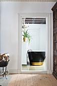 Blick durch offene Tür ins Bad auf freistehende Badewanne in Schwarz mit goldenem Streifen