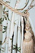 Curtain gathered with beige cord and tassel