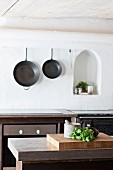 Kitchen utensils on counter and cast iron pans on wall next to arched niche