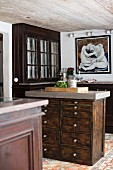 Free-standing chest of drawers made from dark wood with pale worksurface in front of old glass-fronted cabinet in rustic kitchen
