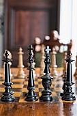Alte, geschnitzte Schachfiguren aus schwarz lackiertem Holz auf Schachbrett