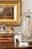 Miniature female figurine wearing lace dress under glass cover behind white doe figurine