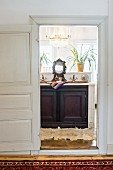 View of washstand with dark wooden base unit seen through open door