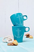 Blue mugs with anchor motifs in cross-stitch look