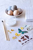 Craft utensils for decoupage Easter eggs: butterfly motifs, paintbrush and glass pot of glue