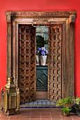 Bodenlaterne aus Messing und Pflanzentöpfe vor halb geöffneter Flügeltür aus geschnitztem Holz in orientalischem Stil, Blick auf Blumentopf auf Fensterbank