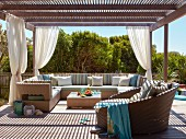 Roofed lounge area with outdoor furniture on wooden terrace in summer sunshine