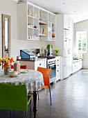 Bright, light-flooded kitchen with easy-care concrete floor, open-fronted shelves, round dining table with colourful chairs and bench with storage solution below window