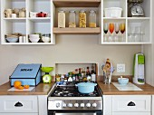 Kitchen counter with cooker flanked by worksurfaces below open-fronted shelves with easy access to crockery & kitchen utensils