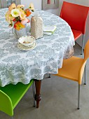 Round table with floral tablecloth and modern, brightly coloured chairs