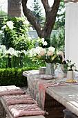 Gedeckter Steintisch und Bank im französischen Antikstil mit Polsterkissen und Toile-de-Jouy Tischläufer, blühender Garten im Hintergrund