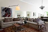 Nest of coffee tables and pale grey corner sofa with colour-coordinated scatter cushions in open-plan interior
