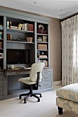 Cream office chair at pale grey shelving with integrated desk and plasma screen