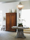 Bowl of orchids on round, solid-wood table, designer pendant lamp and antique wooden cupboard in elegant interior
