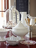 White tureen with lid, citrus squeezer, bowl, pastries under glass cover and jugs