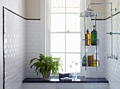 Shelves of toiletries hung on glass partition, black stone shelf below lattice window and white-tiled walls