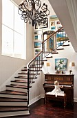 Spacious stairwell with winding staircase and wrought iron chandelier; little girl playing on piano