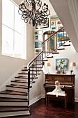 Grosszügiges Treppenhaus mit Wendeltreppe und schmiedeeisernem Lüster; kleines Mädchen am Klavier