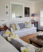 Pale sofa set with scatter cushions below large mirror on wall in bright living room