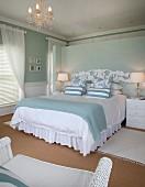 weiße Bettwäsche und pastellblaue Tagesdecke auf Doppelbett mit Trennwand als Bettkopfteil