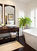 Bathtub below window, antique washstand with countertop basins below framed mirrors and fern on plant stand in corner