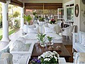 Wooden coffee table and comfortable, pale sofa set on roofed terrace with Doric columns