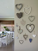 Various love-hearts made from different materials on grey-painted wall; view of set dining tabla and white rattan chairs to one side