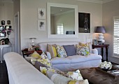 Sofa set with scatter cushions in bright living room with country-house ambiance
