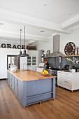 Kücheninsel mit grau lackiertem Unterschrank in offener Küche