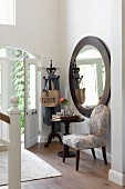 Upholstered chair and bistro table below large round mirror on foyer wall
