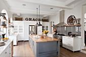 Grosszügige, offene Küche mit Mittelblock, Holz Arbeitsplatte auf grau lackiertem Unterschrank