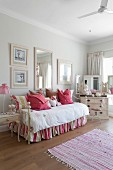 Couch with striped, loose cover below framed pictures on wall and chest of drawers with dressing table mirrors