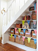 Storage shelves under staircase decorated with bunting