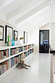 Bücherregal im niedrigen Kniestockbereich eines Galeriegangs, davor ein liegender Hund
