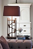 Table lamp with delicate wooden base and brown lampshade in living room