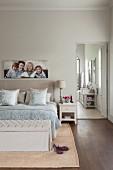 Schlafzimmer in Naturfarben mit Familienbild, offene Tür zum Bad Ensuite