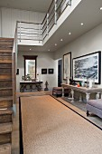Bright, spacious hallway with antique stone table, black-framed pictures, staircase with wooden treads and metal gallery balustrade