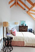 Black side table next to double bed with pale bedspread in attic room with exposed wooden ceiling beams
