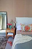 Kissen mit buntem, folkloristischem Stoffbezug auf Bett, seitlich Nachttisch aus Massivholz vor Wand