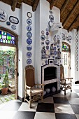 Antique chairs flanking tiled fireplace below decorative plates on walls; open terrace doors leading to courtyard on either side