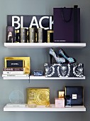 Various perfumes and ladies' accessories on white floating shelves
